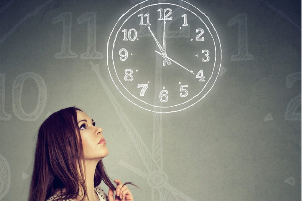 woman looking at a clock