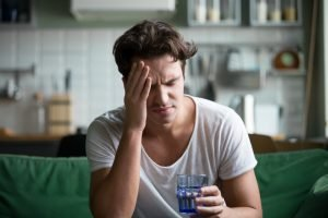 Young man is hungover and touching his forehead like he has a headache and holding a glass of water