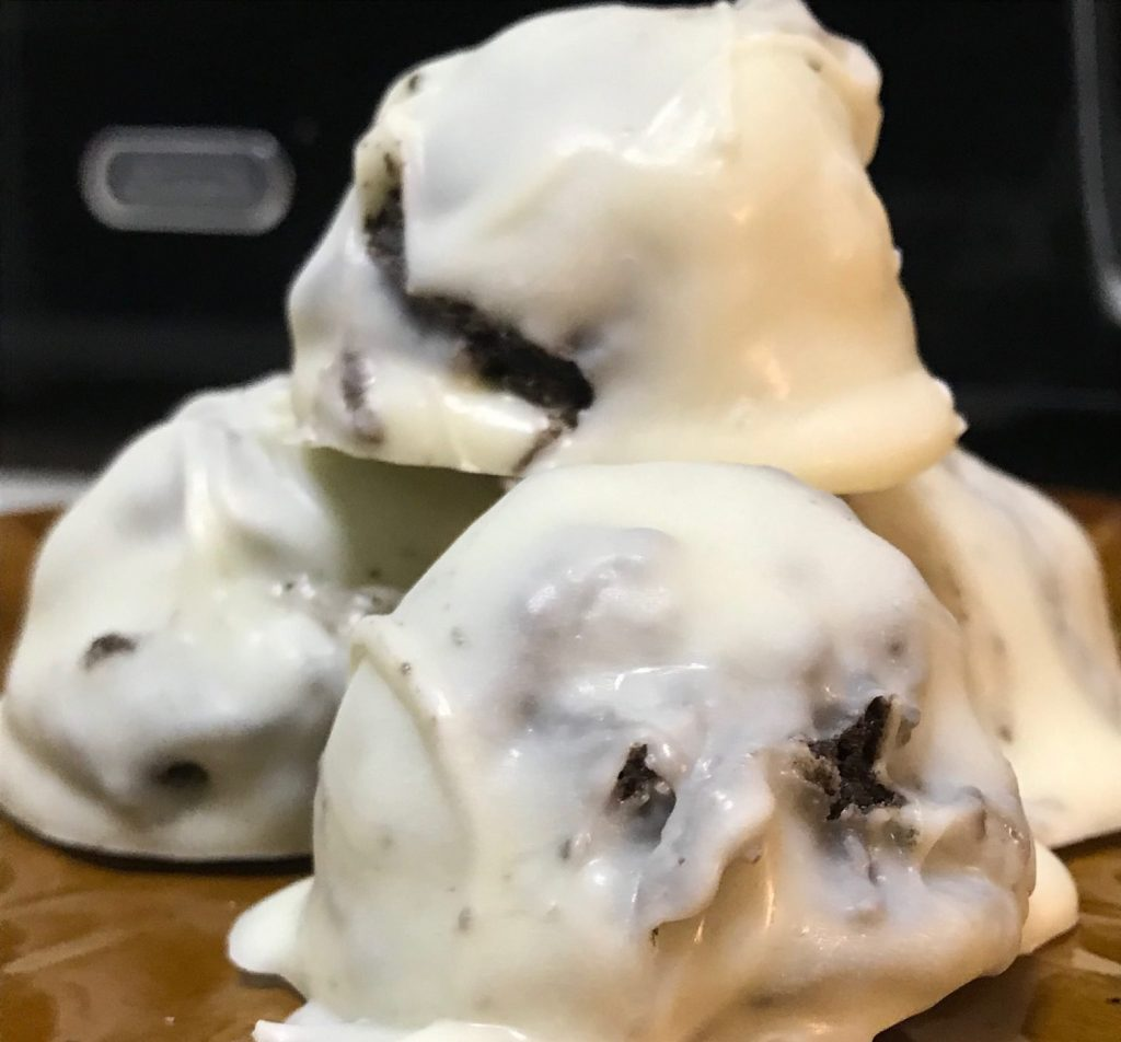 cbd infused oreo balls with white chocolate coating on a plate