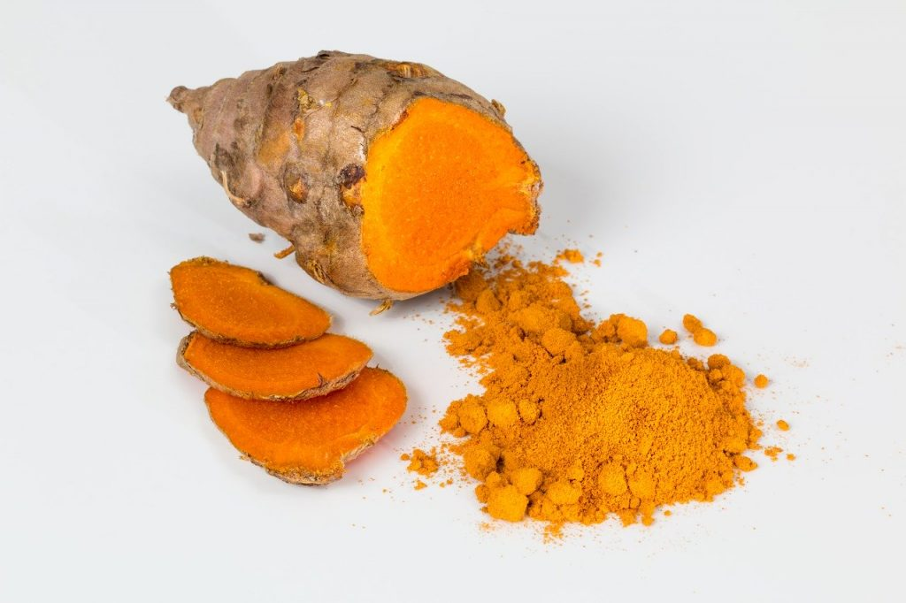 raw turmeric being shaved into powder
