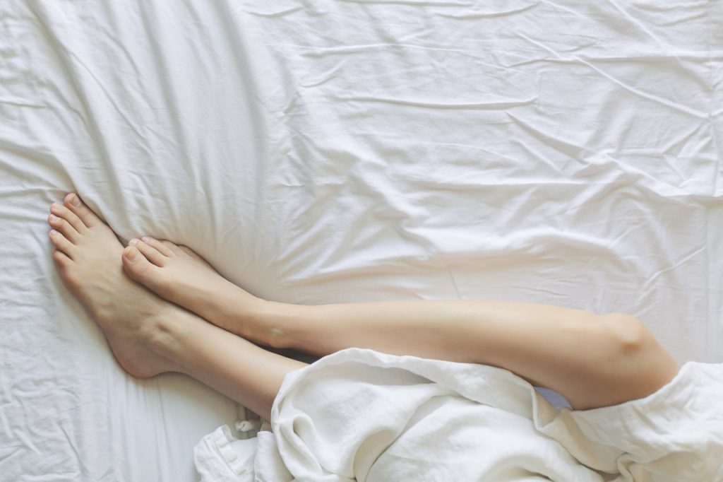 woman legs under covers in bed