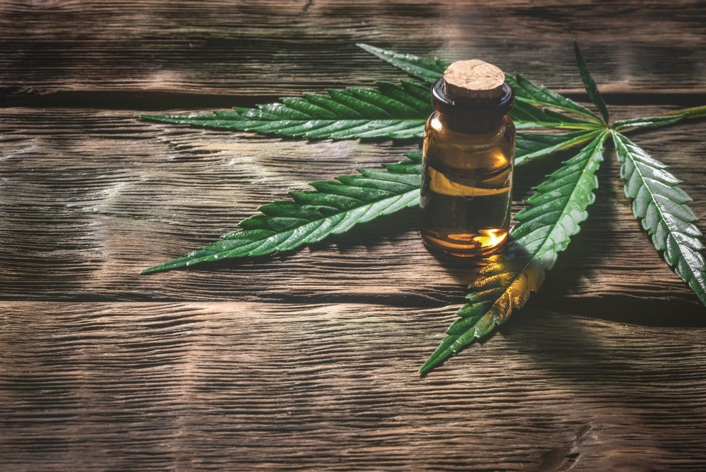 cbd oil in bottle with leaf on a wooden table
