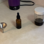 a funnel, tincture bottle, and glass jar with full spectrum cbd oil on counter