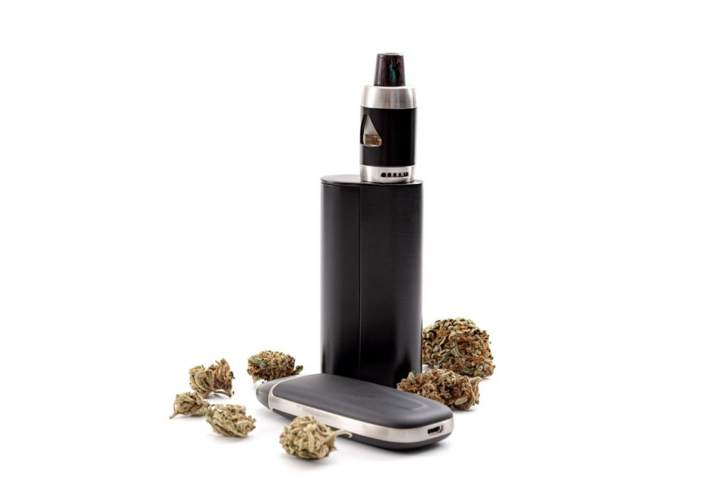 dry herb vaping device surrounded by cbd flower buds